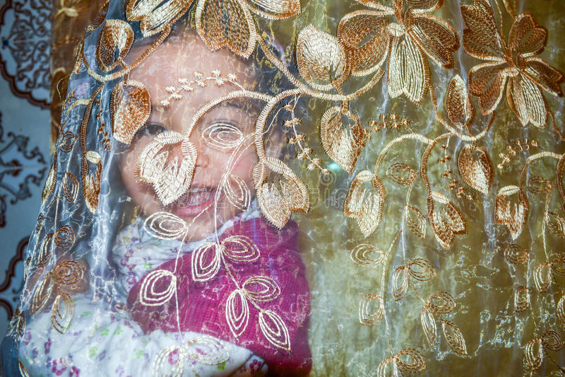 Liten flicka som ler bak genomskinliga gardiner