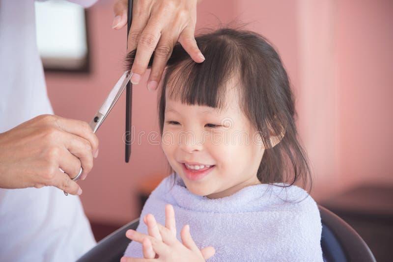Liten flicka som ler den vita frisören som klipper hennes hår royaltyfri bild