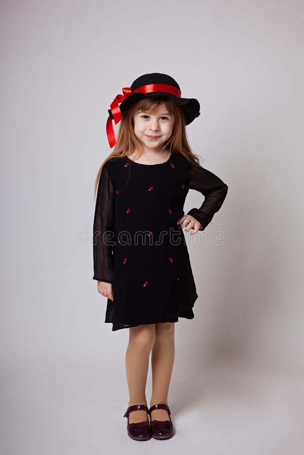 Liten flicka som ler i en svart klänning och en svart hatt med en röd ri arkivbild