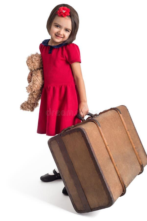 Liten flicka som ler i röd klänning med resväska- och leksakbjörnen arkivbild