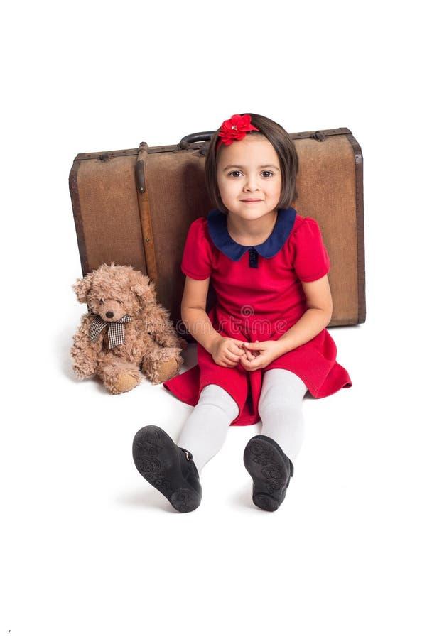 Liten flicka som ler med resväska- och leksakbjörnen arkivbild