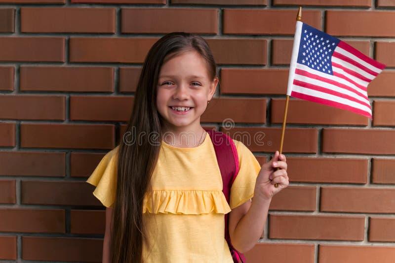 liten flicka som ler och rymmer amerikanska flaggananseende stående mot tegelstenväggen arkivfoto