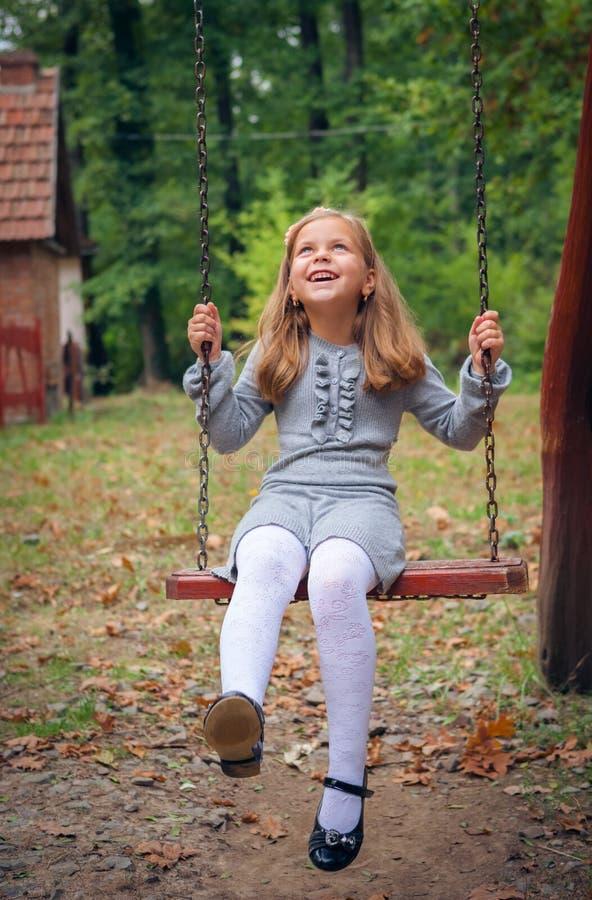 Liten flicka som ler på Swing royaltyfri fotografi