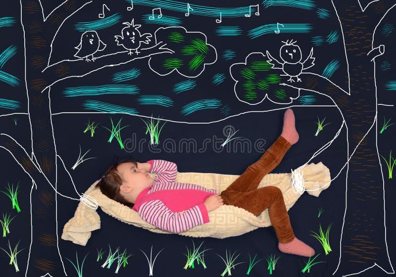 Liten flicka som ligger i en hängmatta arkivfoton