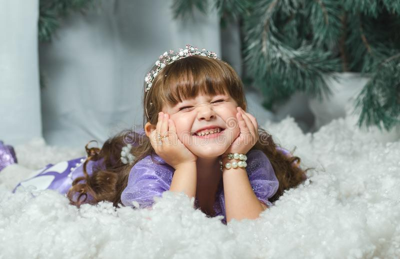 Liten flicka som ligger i snön och ler på bakgrunden av ettträd, photosessionstudior ny year2018, jul arkivbilder