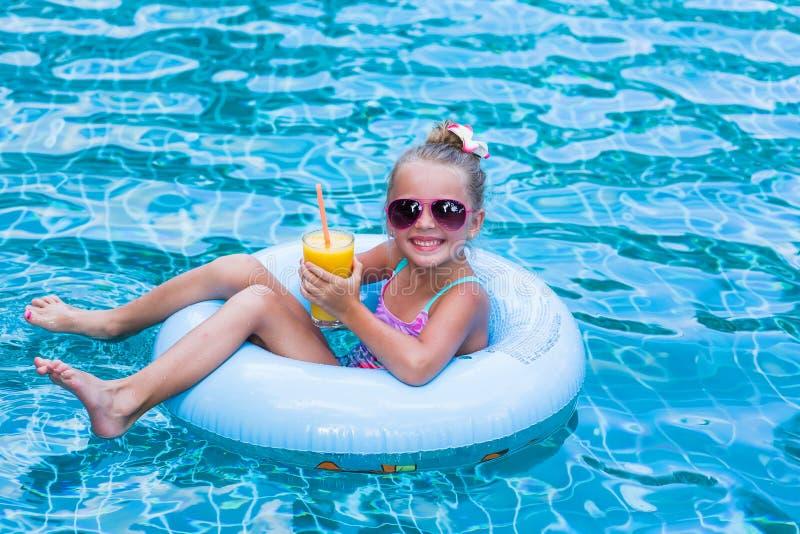 Liten flicka som ligger på den uppblåsbara cirkeln i simbassäng I händerna av ett exponeringsglas av mangofruktsaft ferier royaltyfri fotografi