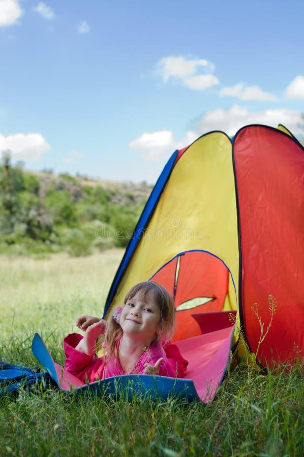Liten flicka som ligger på det matta near färgrika tältet royaltyfria foton