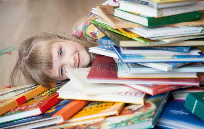 liten flicka som ligger på golvet bland böcker royaltyfria bilder