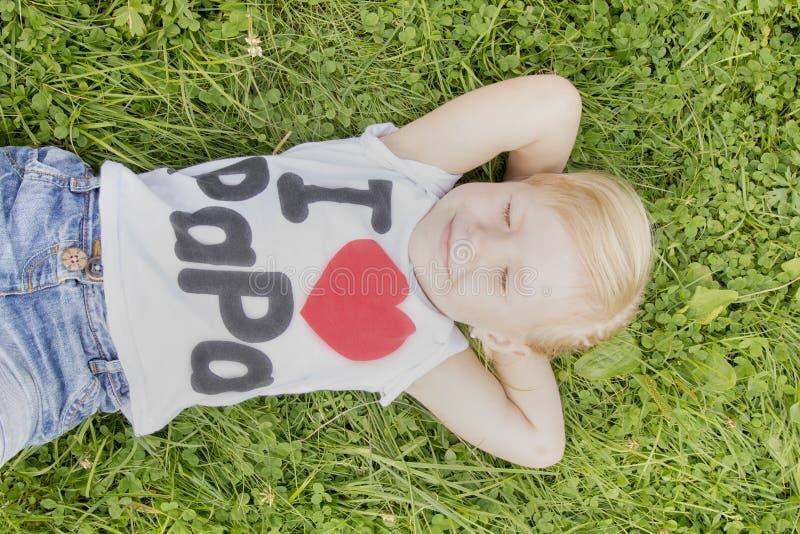 Liten flicka som ligger på gräset och drömma arkivbilder