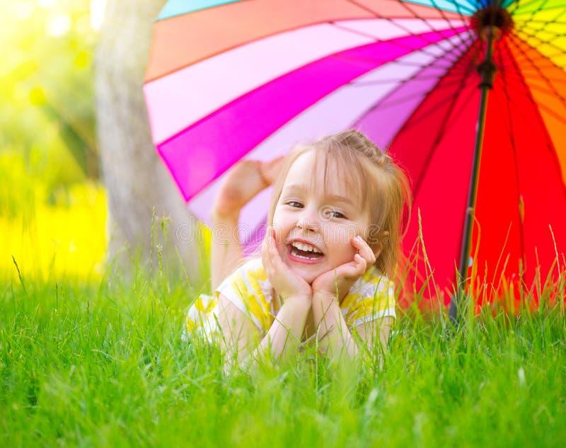 Liten flicka som ligger på grönt gräs under det färgrika paraplyet arkivbilder