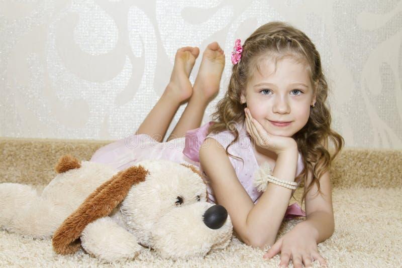Liten flicka som ligger på mattan med en flott hund royaltyfri fotografi
