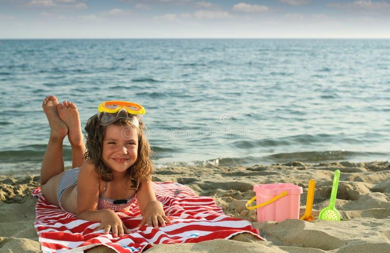 Liten flicka som ligger på strandsommarsäsong royaltyfri bild