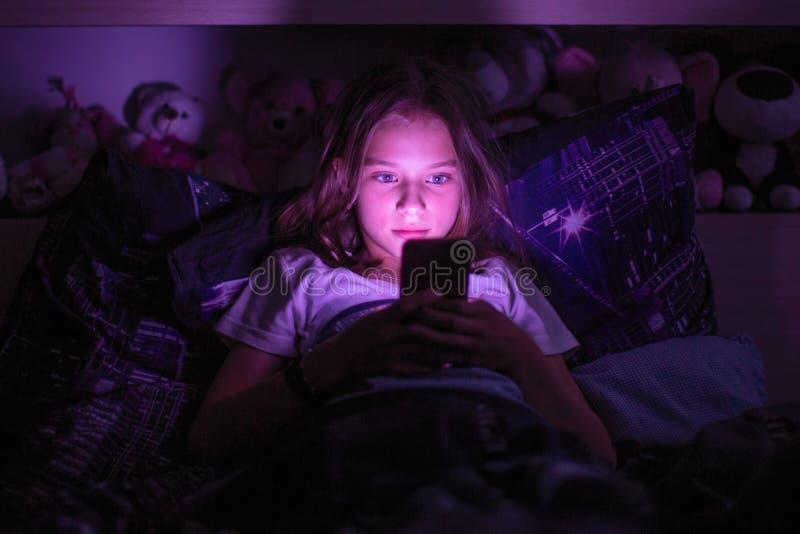 Liten flicka som ligger under en filt som ser smartphonen royaltyfria bilder