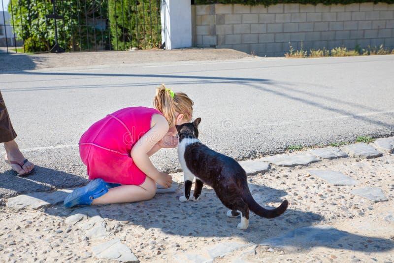 Liten flicka som lyssnar till den vita och svarta katten på gatan royaltyfri bild