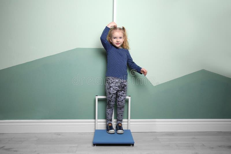 Liten flicka som mäter hennes höjd royaltyfri foto