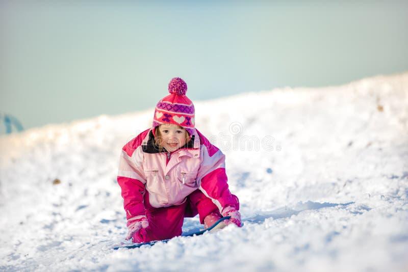 Liten flicka som ner faller i snö arkivfoton