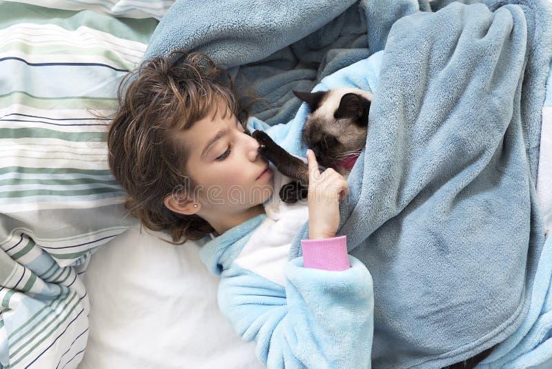 Liten flicka som ner ligger på sängen med hennes katt royaltyfria bilder