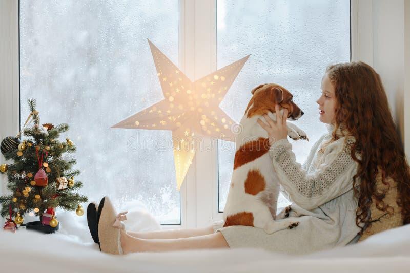 Liten flicka som omfamnar hennes valphund och att sitta på fönster och waiti arkivfoto