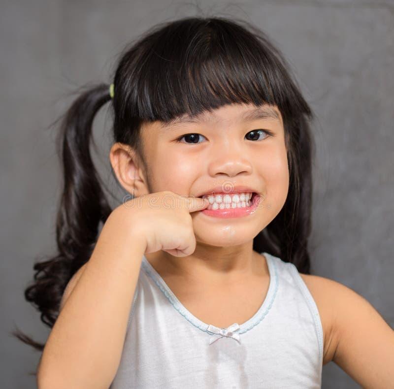 Liten flicka som pekar tänder på vit, når att ha borstat tänder som känner sig lyckliga arkivbild