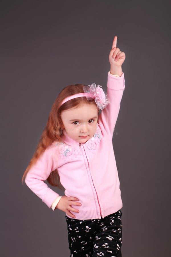 Liten flicka som pekar uppåt i studion royaltyfria foton