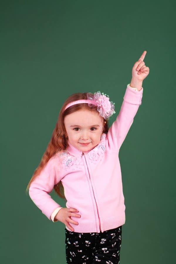 Liten flicka som pekar uppåt i studion royaltyfri fotografi