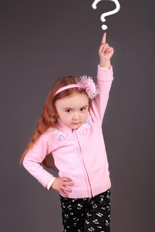 Liten flicka som pekar uppåt i studion royaltyfri foto