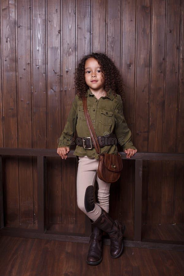 Liten flicka som poserar mot bakgrunden av en trävägg arkivfoton