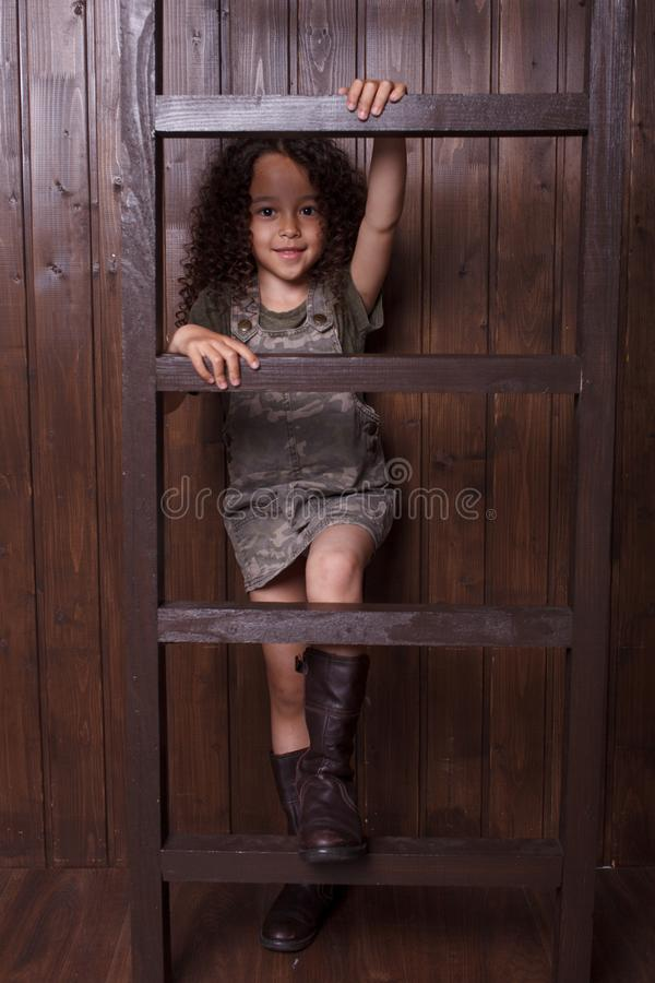 Liten flicka som poserar mot bakgrunden av en tr?v?gg arkivfoto