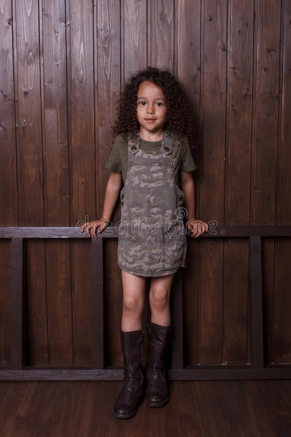 Liten flicka som poserar mot bakgrunden av en tr?v?gg royaltyfri fotografi