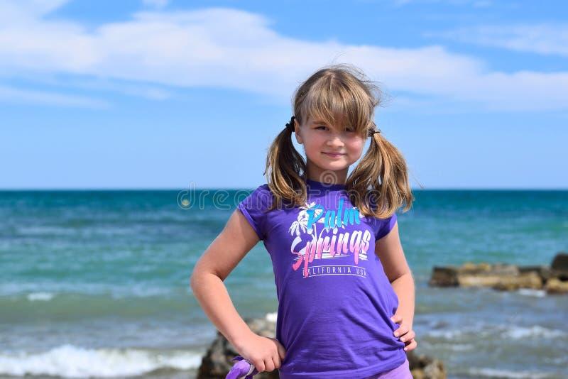 Liten flicka som poserar på stranden arkivbild