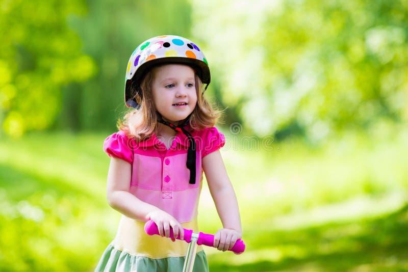 Liten flicka som rider en färgrik sparkcykel arkivbild