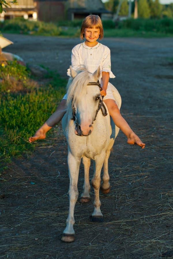 Liten flicka som rider en häst royaltyfria foton
