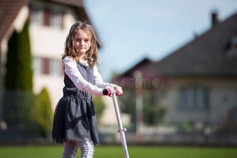 Liten flicka som rider en sparkcykel på en sportlätthet royaltyfria foton