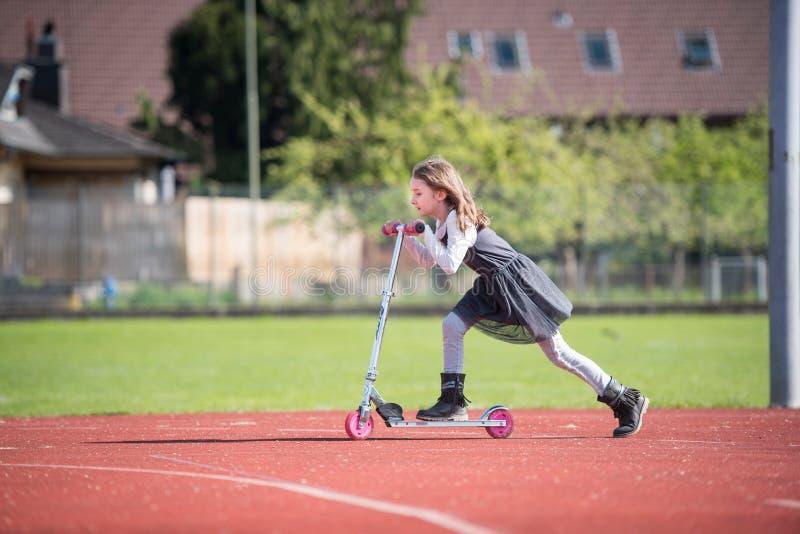 Liten flicka som rider en sparkcykel på en sportlätthet arkivfoton