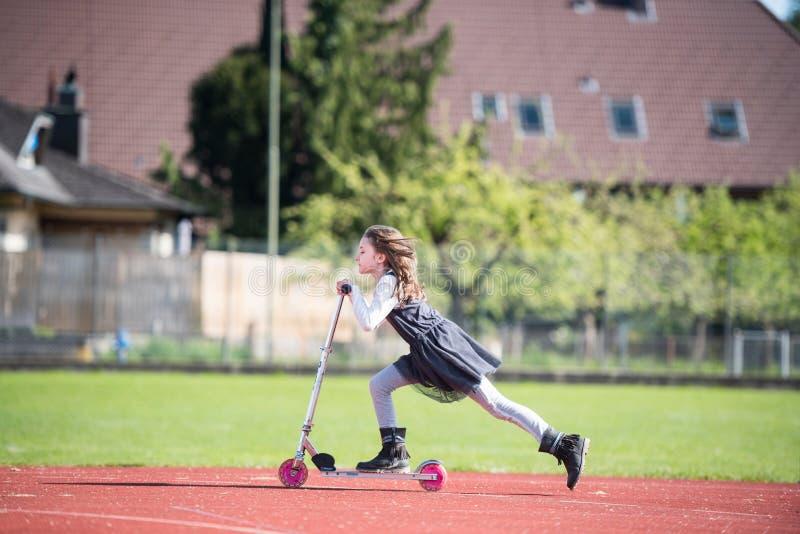 Liten flicka som rider en sparkcykel på en sportlätthet royaltyfria bilder