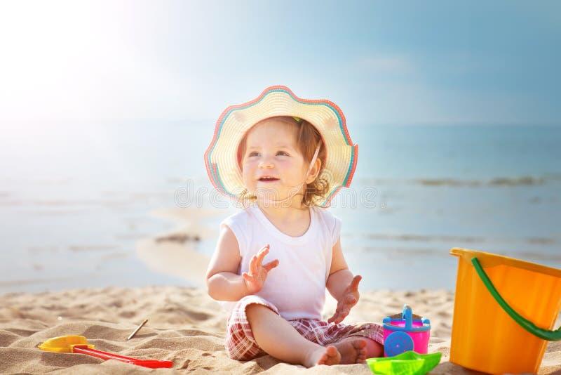 Liten flicka som ropar på havet med hinken royaltyfri fotografi
