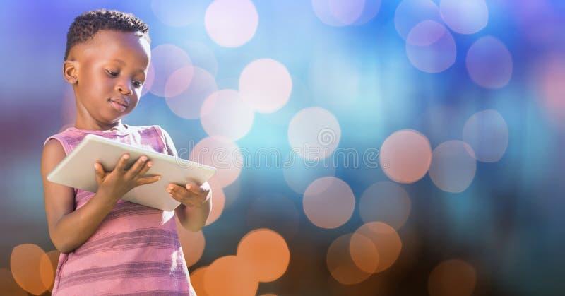 Liten flicka som rymmer den digitala minnestavlan över suddighetsbakgrund royaltyfri foto