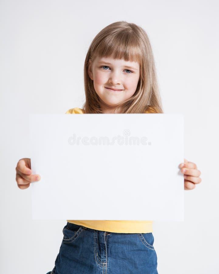 Liten flicka som rymmer det tomma arket av ett papper royaltyfri fotografi