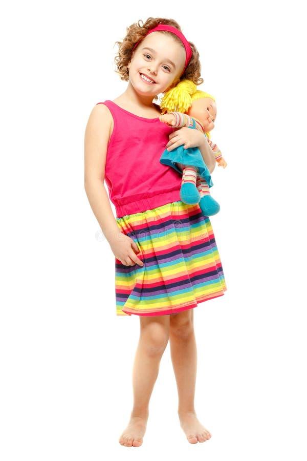 Liten flicka som rymmer en docka. Vit bakgrund arkivbild