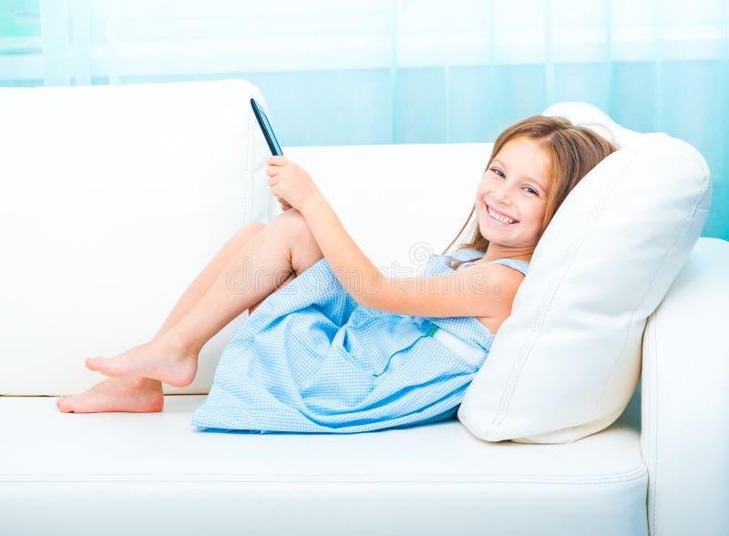 Liten flicka som rymmer en eBook royaltyfri foto