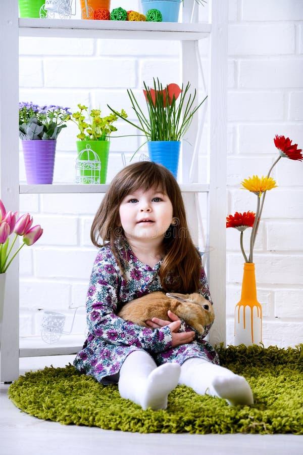 Liten flicka som rymmer en fluffig kanin med blommor omkring arkivfoto