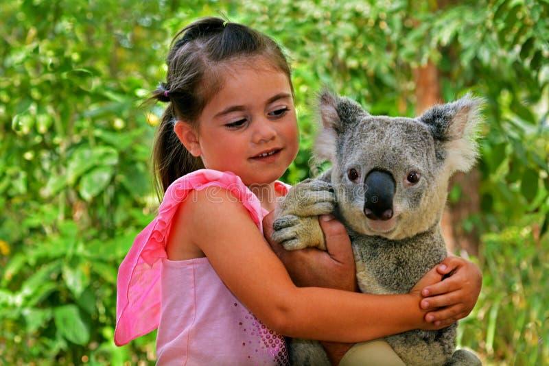Liten flicka som rymmer en koala royaltyfri foto