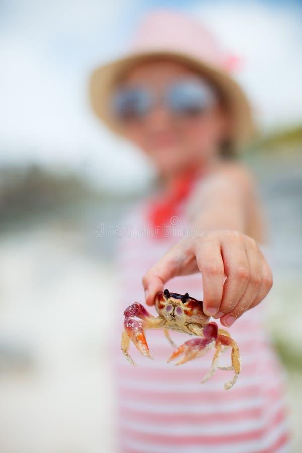 Liten flicka som rymmer en krabba royaltyfri foto
