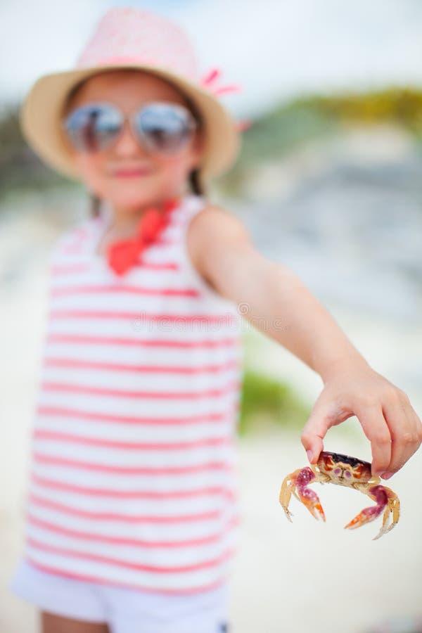 Liten flicka som rymmer en krabba fotografering för bildbyråer