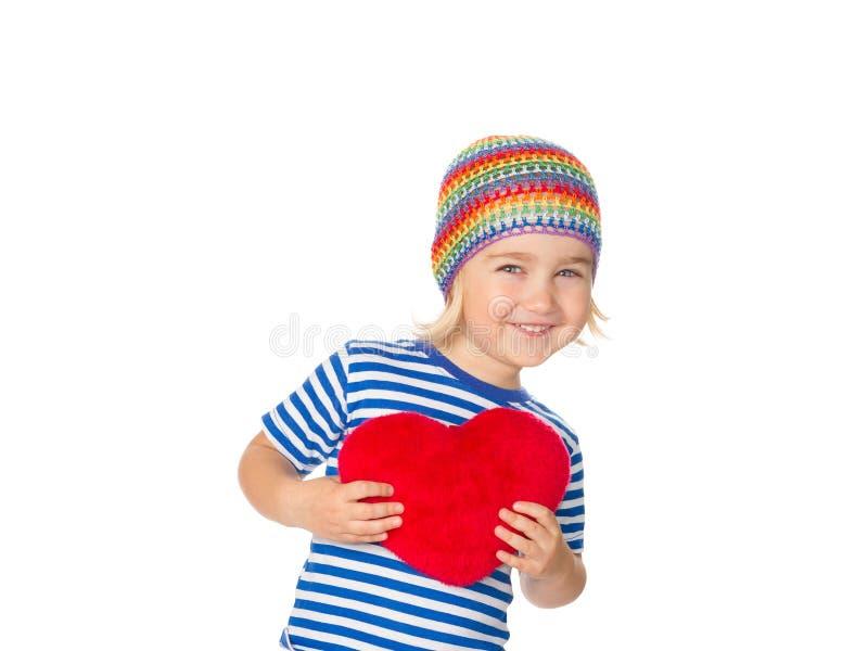 Liten flicka som rymmer en röd hjärtaleksak arkivfoto