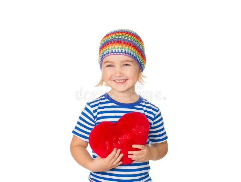 Liten flicka som rymmer en röd hjärtaleksak royaltyfria foton