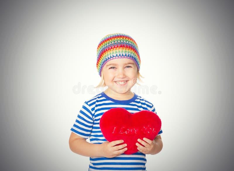 Liten flicka som rymmer en röd hjärtaleksak royaltyfri bild