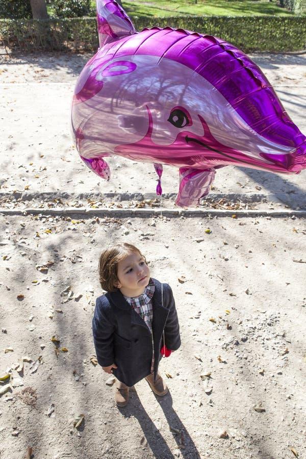Liten flicka som rymmer en stor ballongdolpin formad arkivbild