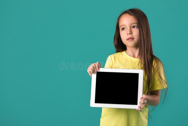 Liten flicka som rymmer en tom minnestavladator arkivfoto