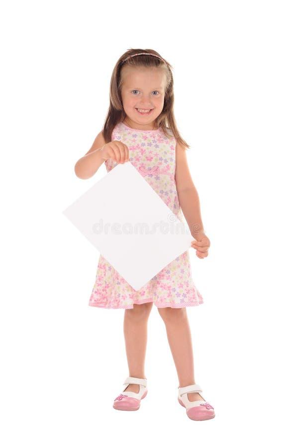 Liten flicka som rymmer ett ark av papper arkivfoto